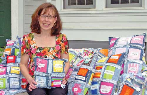 Virginia Kerrigan surrounded by colorful, handmade pillows and blankets